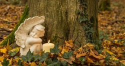 Angel with candle, nature cemetery