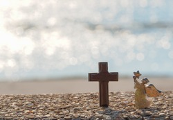 Angel with star in hand and wooden cross on gravel floor with bokeh blue sea as background.Believe in  miracle.Faith in God.Miracle from heaven.Believe in goddess.Christianity background concept.