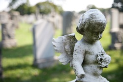 Angel with wings above headstones in cemetery