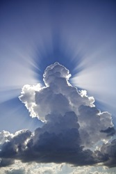 Angelic / antrophomorphic cloud in the sky with sun-rays casting a shadow in the water vapor