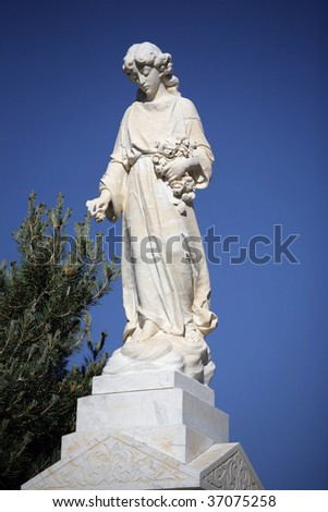 Angelic Cemetery Statue against blue sky.