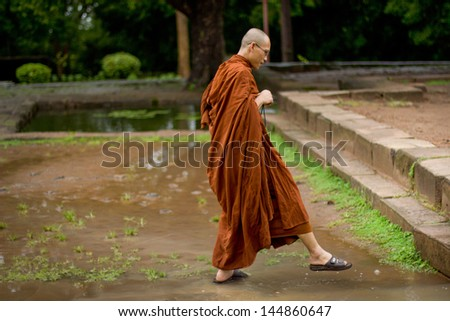 ANGKOR WAT, CAMBODIA - CIRCA OCTOBER 2011: Unidentified monk walking for prays during rain in Angkor Wat. All temples in Ankgor complex were completely flooded after heavy rains in Cambodia in 2011.