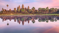 Angkor Wat temple at dramatic sunrise reflecting in water