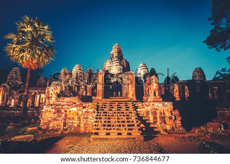Angkor Wat Temple in Cambodia is the largest religious complex, inscribed on UNESCO World Heritage List. Ancient Khmer architecture. Orange ancient ruins against blue night sky. Retro vintage toning #736844677