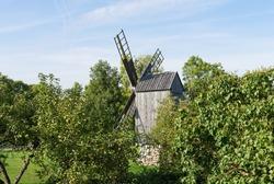 Angla Estonia - September 11 2021: Typical old wooden trestle  type windmill hidden between trees on island Saaremaa. Sunny early autumn day.