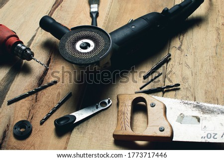 Angle grinder with drill and metal bits on wooden table. carpentry, metalworking and repairs concept.