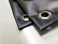 Angle grommets on printed black advertising banner - Image