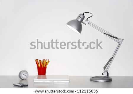 Angle poise lamp, laptop, clock, pencil holder and cellphone on desk