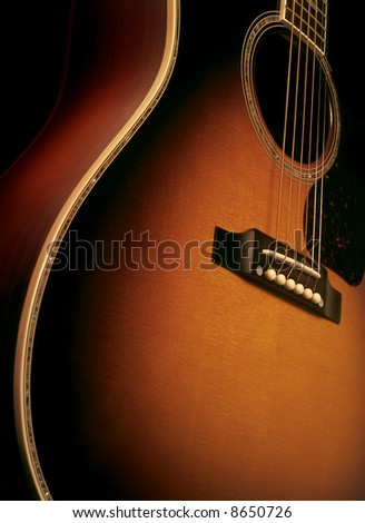 Angle shot of a maple wood acoustic guitar showing wood grain, bridge and strings.