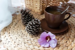 Angle view of brown cup of herbal tea, two pine cones and gentle flower on straw table. and light background Healthy lifestyle, organic beverages, alternative medicine.