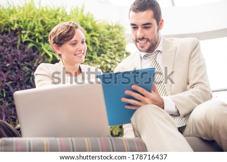 Angle view of cheerful businesspeople cooperating at a cafe on the foreground
