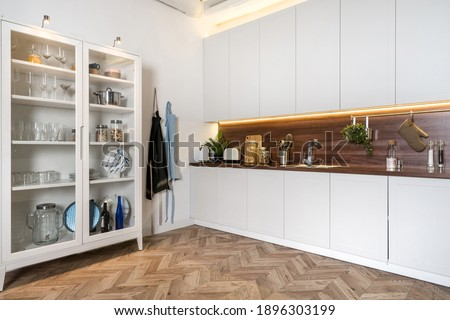 Angle view of modern interior with white kitchen cupboards, kitchenware cabinet, apron on hook and wood countertop. Copy space on wooden floor Photo stock ©