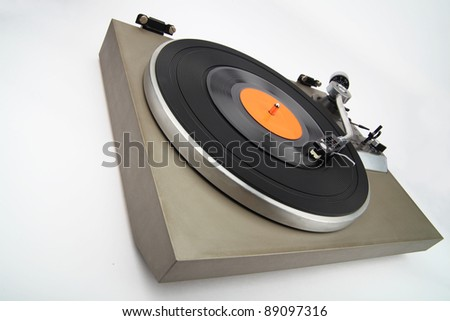 Angle view of vintage turntable with vinyl phonorecord - stock photo