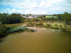Angled aerial photo of murky brown suburban wetland lake with green foliage, sunny blue sky with clouds, green grass and overland powerlines.