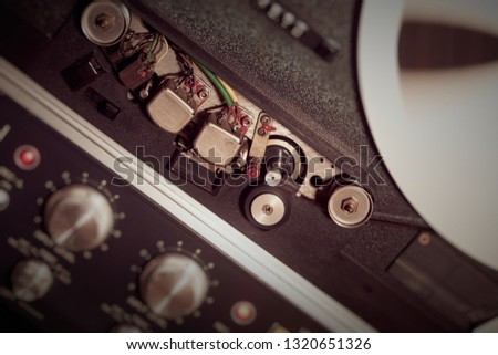 Angled close up of reel to reel heads and a spinning spool on a vintage reel to reel tape deck. #1320651326