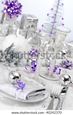 Angled festive Christmas holiday table setting with silver and purple theme, focus on stem of antique wine glass