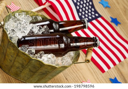 Angled horizontal photo of glass bottled beer in old metal bucket filled with ice and American flags in background for celebration of Independence Day