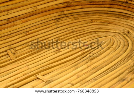 angled interior of a woven brown basket showing the curving of the reeds #768348853