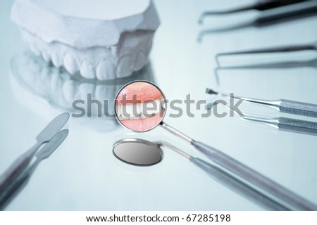 Angled mirror with smile reflection , dental instruments and gypsum dentures