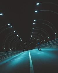Angled shot of a skater on a road at night. Valmieras bridge, Valmiera, Latvia.