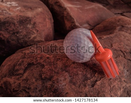 Angled side profile view of white ball with orange brush tee placed on rocky surface highlighting golfing skills challenges.