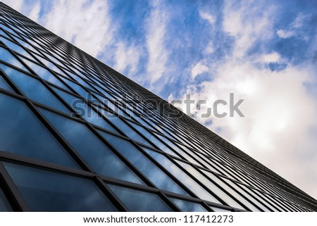 Angled view of a glass wall of an office building. Infinity effect in the blue sky.