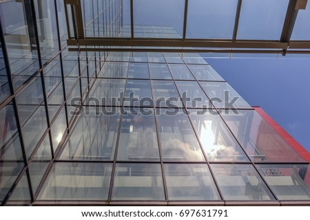 Angled view of a glass wall of an office building. Infinity effect in the blue sky. #697631791