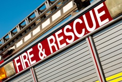Angled view of FIRE & RESCUE sign on the side of a British ladder and pump fire engine, against a clear blue sky.