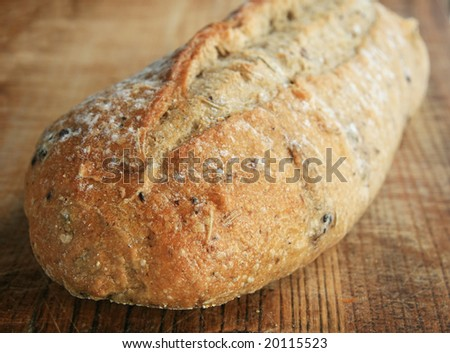 angled view of rosemary kalamata olive bread on wooden cutting board