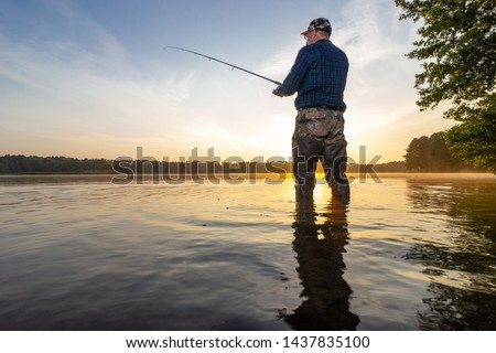 Angler catching the fish during sunrise