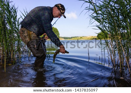 Angler catching the fish in the lake. Catch and release practice within recreational fishing