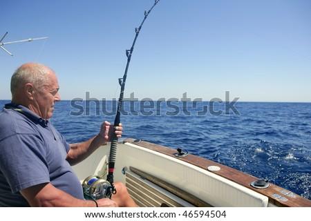 Angler elderly big game sport fishing boat blue summer sea sky