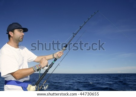 Angler fisherman trolling rod and reel fighting saltwater fish