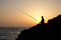 angler on sunset fishing on sea