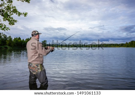 angler standing on the lake shore during cloudy day #1491061133