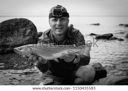 Angler with lake trout in monochromatic portrait #1150435583