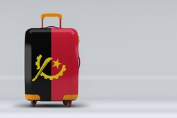 Angola national flag on a stylish suitcases on color background. Space for text. International travel and tourism concept. 3D rendering.