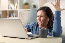 Angry adult woman watching video online on laptop sitting on the floor at home