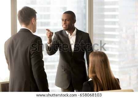 Angry african-american businessman threatens colleague, conflict between male workers at workplace, bullying and discrimination, black boss blames white employee responsible for failure, your fault