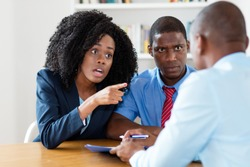 Angry african american couple rejecting contract offer of real estate agent