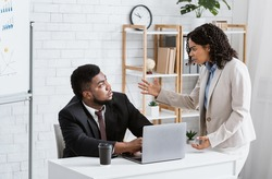Angry African American lady boss scolding male employee for error in urgent project at office. Displeased businesswoman reprimanding black worker for missed deadline. Workplace stress concept