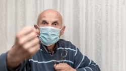 angry aggressive elderly man wearing face mask showing big fist self isolation and coronavirus concept white background
