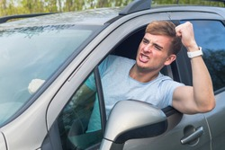 Angry aggressive guy, young emotional irritated man driver screaming, shouting, yelling while driving car, threatening with a fist from automobile window. Driving anger negative emotion, agression