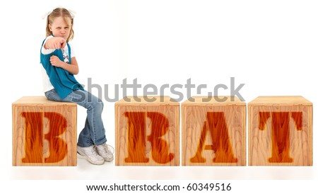 Angry american 7 year old girl sitting on blocks spelling the word brat over white background. Stock fotó ©