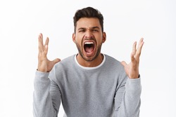 Angry and disappointed handsome bearded man in grey sweater swearing and cursing everyone as lost bid, shaking hands outraged and distressed, losing temper yelling upset, express fury and sadness