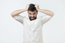 Angry and furious man on a gray background. He pulls out his hair in a rage
