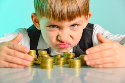 Angry and greedy child holds their money coins. The concept of greed, greed and vice from childhood.