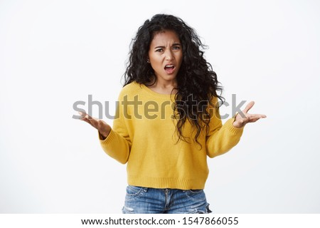 Angry and outraged african american curly-haired girlfriend freak-out, looking pissed as complaining, raise hands in dismay cringe from anger and disappointment, standing white background