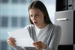 Angry annoyed young businesswoman employee reading letter, working with correspondence, frustrated stressed woman received bad news, holding document, dismissal or debt notification