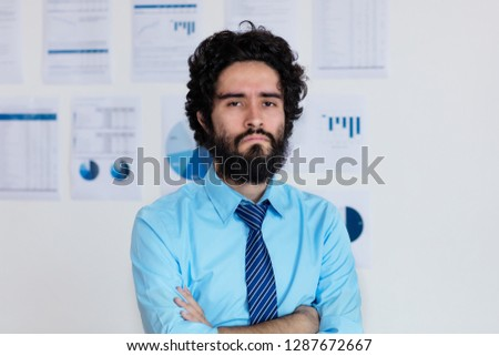 Angry arabic businessman with beard and tie at office of company